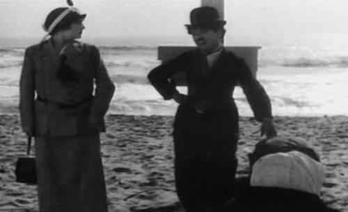 Chaplin tiếp cận Edna trong khi hai người chồng đang xông vào đánh nhau.