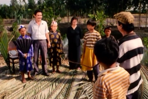 Đoàn tuồng của anh Tư ghé thăm một vùng quê trong phim ''Dòng Sông Cười''